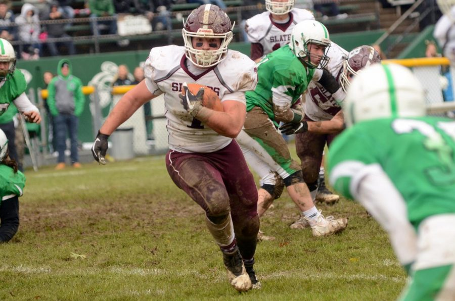 INTO THE FRAY Joey Schrader, Bangorian football star, carries the pigskin behind enemy lines.